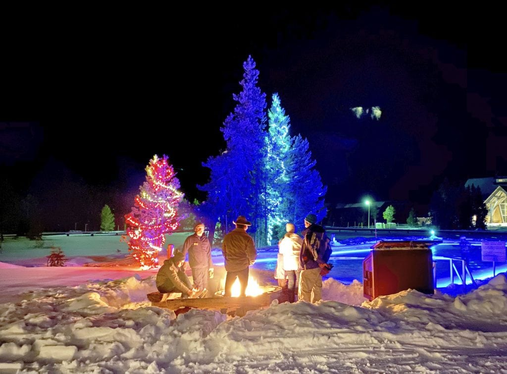 Winter in Yellowstone: people chatting around fire pit outside the Snow Lodge